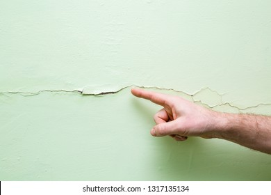 Man's hand finger pointing to cracked wall in house. Building problems and solutions concept. Closeup.