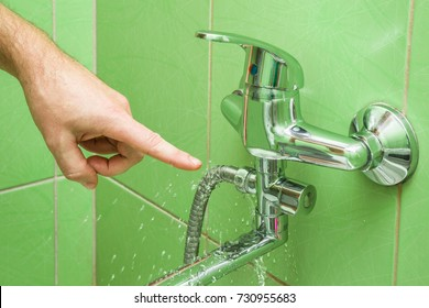 Man's hand finger pointing to a damaged leaking water tap hose in the bathroom of house, flat or other place. Plumbing concept.