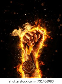 Man's hand in a fire is holding up gold medal on a dark background. Winner in a competition.
