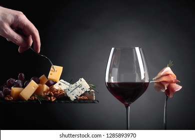 Man's hand with a fork, taking a piece of cheese. Glass of red wine with various cheeses , fruits and prosciutto on a dark background.