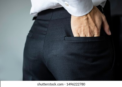 The man's hand is fumbling behind the black trousers.Men wearing white shirts pickpockets on black slacks.