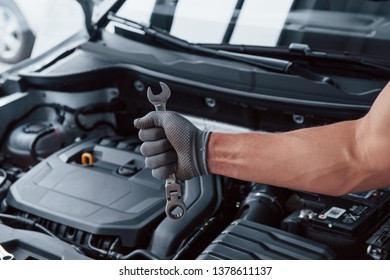 Man's hand in glove holds wrench in front of broken automobile.