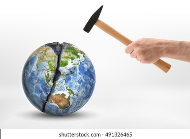 Man's hand with a hammer hits the planet Earth. Anthropogenic impacts. Environmental effects. Harm and damage. Elements of this image are furnished by NASA