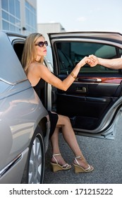 Man's hand helping elegant woman stepping out of car at airport terminal