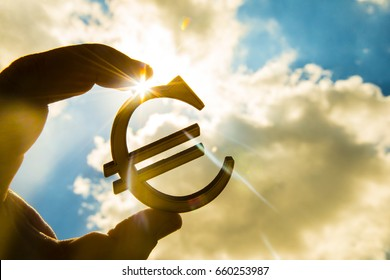 man's hand hold the Euro icon silhouette against sunny blue and yellow sky. sun rays. euro sign, symbol of money, idea of Euro Union