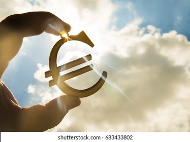 man's hand hold the Euro icon silhouette against sunny blue and yellow sky. sun rays. euro sign, symbol of money, idea of Euro Union, sun rays beam