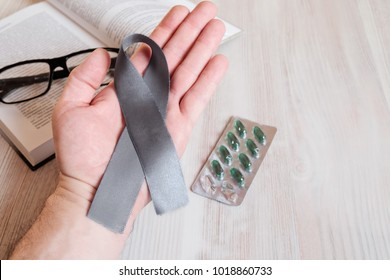A man's hand hold a gray ribbon of awareness of Parkinsons disease. As a symbol of Parkinsons Day.