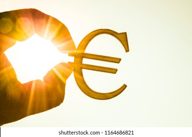 man's hand hold wooden Euro sign against sunny blue and yellow sky. sun rays. euro sign, symbol of money, idea of Euro Union