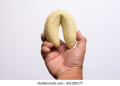 man's hand holding a banana like a big penis symbolizes lack of erection and impotence