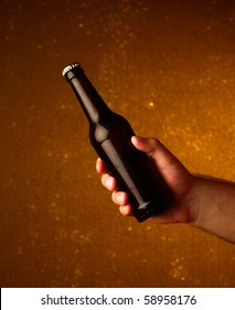 a man's hand holding a beer bottle on orange background