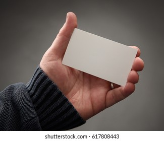 A man's hand is holding a blank white business card template to insert your graphic design on it for a mockup or branding idea.