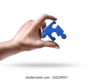 Man's hand holding blue puzzle isolated on white background