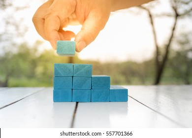 Man's hand holding blue wooden block on white wooden table. Building of steps, Learning and development concept.