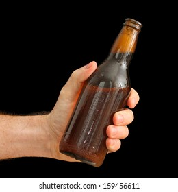 Man's Hand holding a Brown Bottle of Beer isolated on black