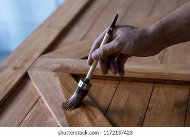 a man's hand holding a brush paints a wooden door