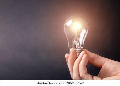 A man's hand holding a burning light bulb.