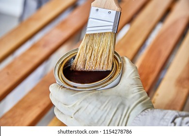 Man's hand holding a can of clear coat wood varnish to treat birch wood slats with shallow depth of field
