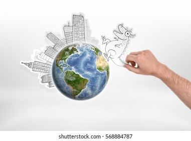 Man's hand holding cartoon funny monster going to attack city put around the globe on. Ecology and Urbanization. Creativity and art. Fantasy and science fiction. Elements of this image are furnished