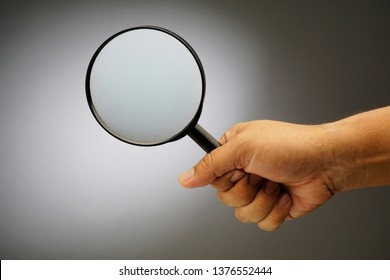 Man's hand, holding classic styled magnifying glass, close-up isolated on grey background, copy space for your image or text.
