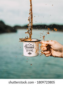 Man's hand is holding a cup of coffee with splashing beverage. Marked cup as adventure