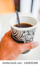 A man's hand holding a cup of hot black coffee by the restaurant window