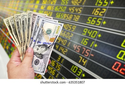 Man's hand holding Dollar (USD) banknotes on stock market background.