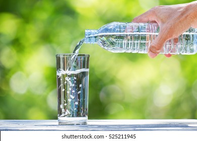 Man's hand holding drinking water bottle and pouring water into glass on wooden table on blurred green nature bokeh background