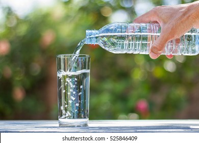 Man's hand holding drinking water bottle and pouring water into glass on wooden table on blurred green bokeh background