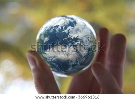 Man's hand holding the Earth with autumn Leaves background, Elements of this image furnished by NASA