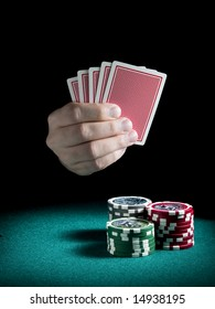 A man's hand holding four cards over three piles of different colors chips on a green felt.