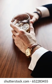 man's hand holding a glass of whiskey