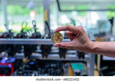 man's hand holding golden Bitcoin on Bitcoin mining background