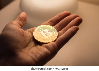 man's hand holding golden Bitcoin