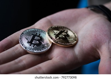 man's hand holding golden and silver Bitcoins