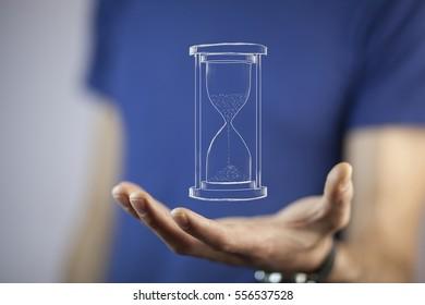Man's hand holding hourglass sand