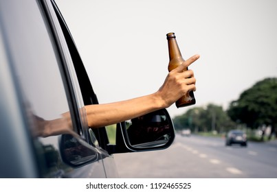 A man's hand is holding a jar of alcohol while driving in the street, driving negligence.