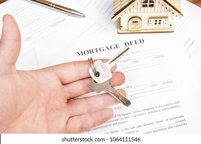Man's hand holding keys of house over mortgage deed.