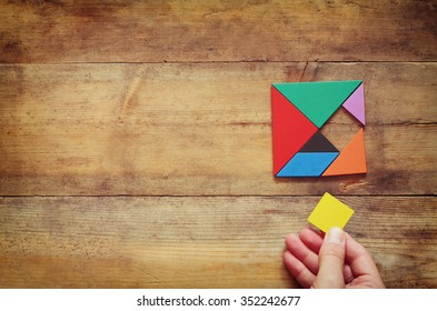 man's hand holding a missing piece in a square tangram puzzle, over wooden table.