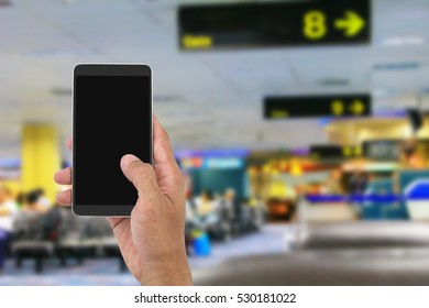 Man's hand holding mobile phone on blurred departure hall in airport