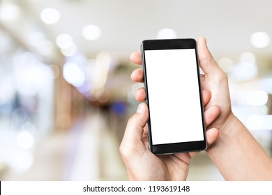 Man`s hand holding mobile smart phone with blank screen at blurred shopping mall background.