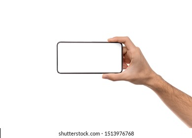 Man's hand holding modern smartphone with blank screen in horizontal orientation for mockup, copy space