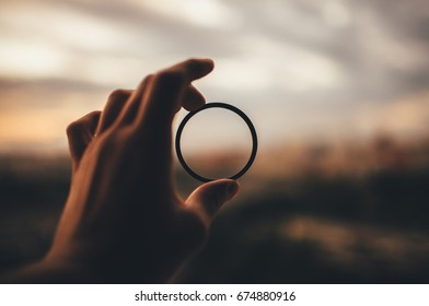 man's hand is holding an optical ring out of focus city