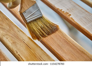 Man's hand holding a paint brush applying varnish to birch wood slats with shallow depth of field