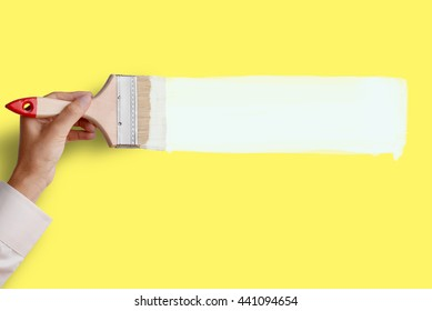 Man's hand holding paintbrush paint white color on yellow color wall, blank space for your text, banner, copyspace, advertising, or your design.