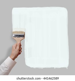 Man's hand holding paintbrush paint white color on gray color wall, blank space for your text, banner, copyspace, advertising, or your design.