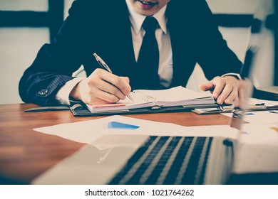 A man's hand holding pen pointing on summary report chart and calculate finance in office.