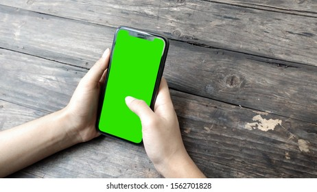 man's hand holding phone a mobile telephone with a vertical green screen in tram chroma key smartphone technology cell phone touch message display hand with wood table
