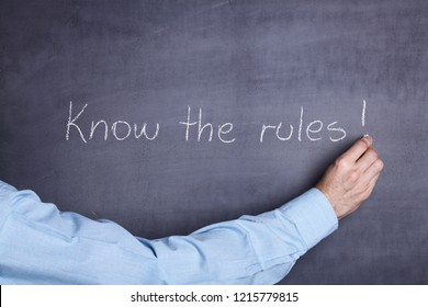 """A man's hand holding a piece of chalk and writing the phrase: """"Know the rules!"""" on a blackboard"""