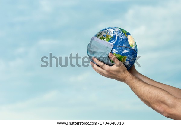 Mans hand holding planet Earth wearing a mask, concept of planet suffering from the COVID-19 pandemic.