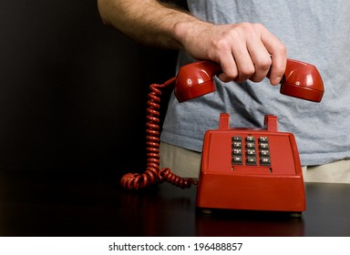 A man's hand holding the receiver of a red phone on the table.